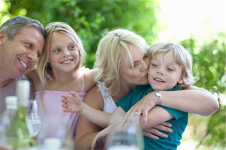Mother kissing son at table outdoors Stock Photo - Premium Royalty-Free, Code: 614-06623613