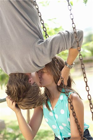 Couple kissing on swing set Stock Photo - Premium Royalty-Free, Code: 614-06623632