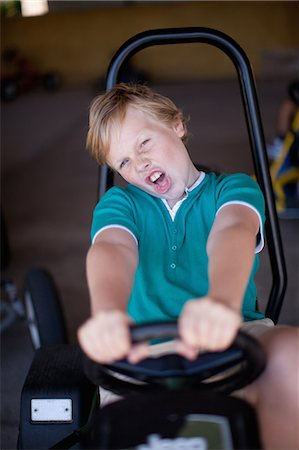preteen open mouth - Boy riding go-kart in garage Stock Photo - Premium Royalty-Free, Code: 614-06623649