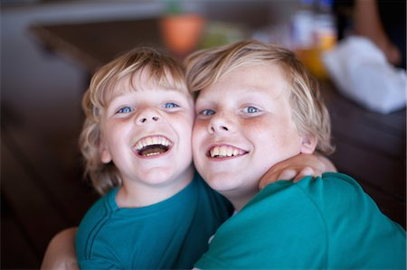 preteen open mouth - Smiling boys hugging in living room Stock Photo - Premium Royalty-Free, Code: 614-06623658