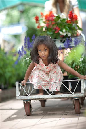 Girl riding in cart in plant nursery Stock Photo - Premium Royalty-Free, Code: 614-06623715