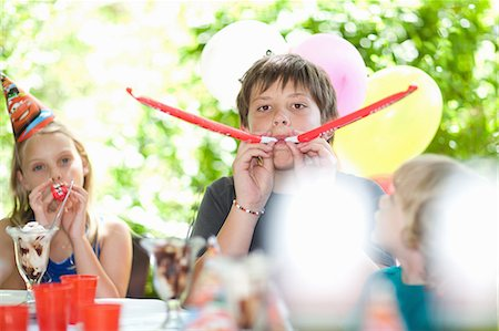 Children blowing noisemakers at party Stock Photo - Premium Royalty-Free, Code: 614-06623758