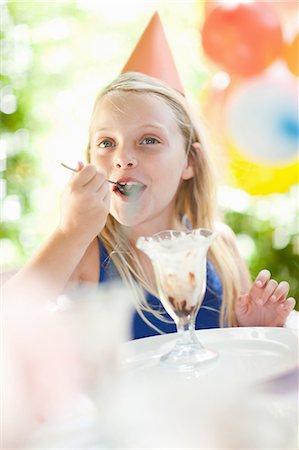 Girl having ice cream sundae at party Stock Photo - Premium Royalty-Free, Code: 614-06623764