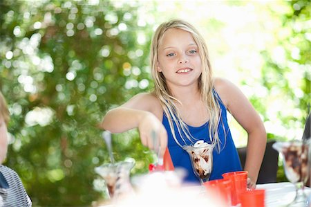 Girl having ice cream sundae at party Stock Photo - Premium Royalty-Free, Code: 614-06623760