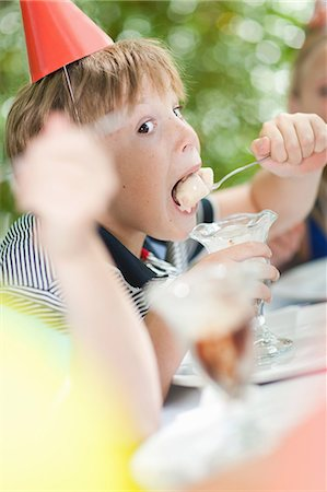 Boy having ice cream sundae at party Stock Photo - Premium Royalty-Free, Code: 614-06623763