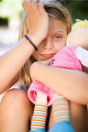 sad girls - Girl holding doll outdoors Stock Photo - Premium Royalty-Free, Code: 614-06623780