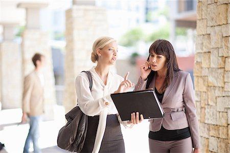 Businesswomen talking in walkway Stock Photo - Premium Royalty-Free, Code: 614-06623833
