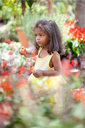 Girl blowing bubbles outdoors Stock Photo - Premium Royalty-Free, Code: 614-06623922