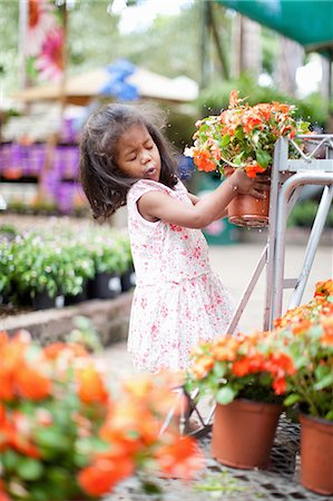 Girl holding potted plant in nursery Stock Photo - Premium Royalty-Free, Code: 614-06623935