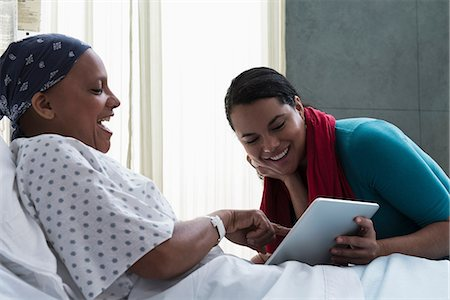 Daughter visiting mother in hospital, showing her digital tablet Stock Photo - Premium Royalty-Free, Code: 614-06718038