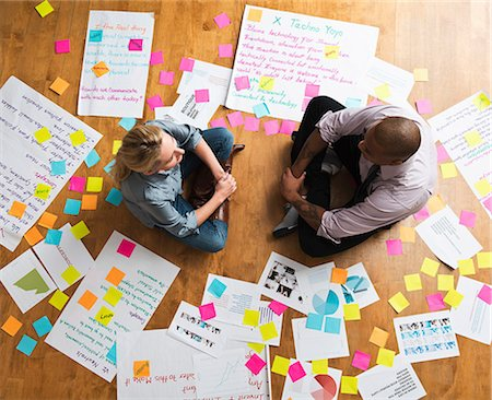 self adhesive note - Colleagues sitting cross legged on floor with papers and adhesive notes Stock Photo - Premium Royalty-Free, Code: 614-06718144