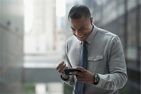 Happy businessman looking at smartphone Stock Photo - Premium Royalty-Free, Code: 614-06718183