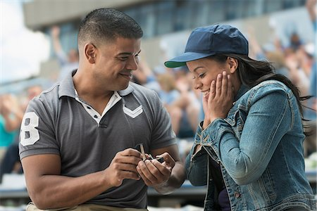 Man proposing to girlfriend at sports game Stock Photo - Premium Royalty-Free, Code: 614-06718194