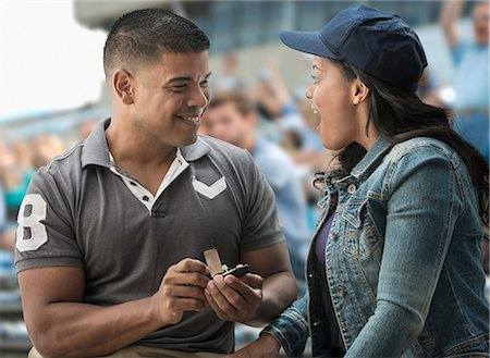 Man proposing to girlfriend at sports game Stock Photo - Premium Royalty-Free, Code: 614-06718193