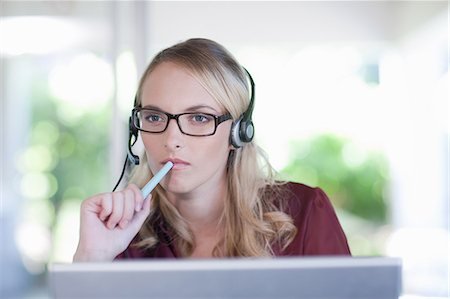 Businesswoman wearing headset at desk Stock Photo - Premium Royalty-Free, Code: 614-06718468