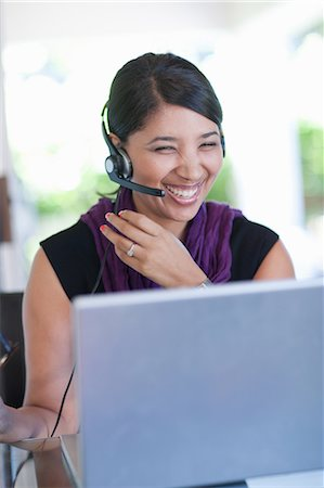 Businesswoman wearing headset at desk Stock Photo - Premium Royalty-Free, Code: 614-06718463