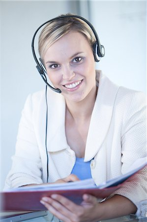 Businesswomen wearing headset at desk Stock Photo - Premium Royalty-Free, Code: 614-06718637