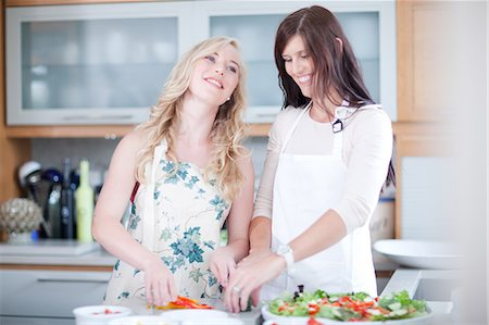 Women cooking together in kitchen Stock Photo - Premium Royalty-Free, Code: 614-06718793