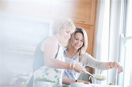 daughter middle-aged mother women young adults - Mother and daughter cooking in kitchen Stock Photo - Premium Royalty-Free, Code: 614-06718803
