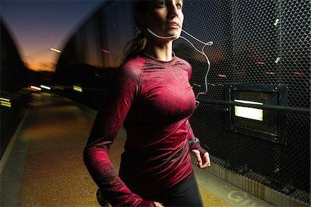 Woman running on pedestrian bridge Stock Photo - Premium Royalty-Free, Code: 614-06718843