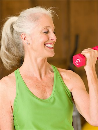 Older woman lifting weights at home Stock Photo - Premium Royalty-Free, Code: 614-06718868