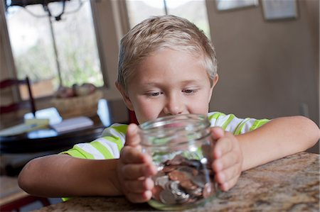 Boy putting savings in glass jar Stock Photo - Premium Royalty-Free, Code: 614-06718940