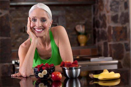 Older woman having fruit in kitchen Stock Photo - Premium Royalty-Free, Code: 614-06719074
