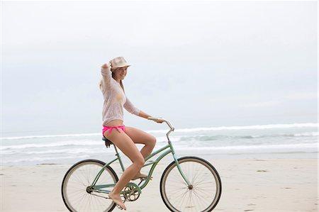 Woman riding bicycle on beach Stock Photo - Premium Royalty-Free, Code: 614-06719151