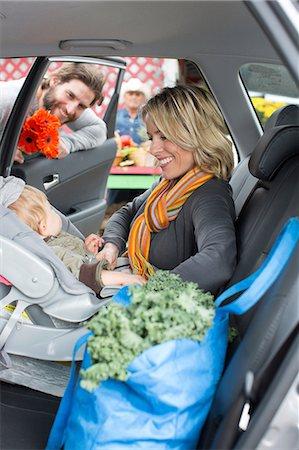 Woman buckling son in car seat Stock Photo - Premium Royalty-Free, Code: 614-06719261