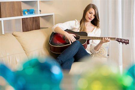 Woman playing guitar on sofa Stock Photo - Premium Royalty-Free, Code: 614-06719306