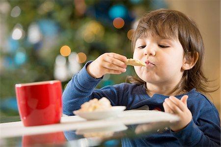 Girl eating Christmas cookies Stock Photo - Premium Royalty-Free, Code: 614-06719320