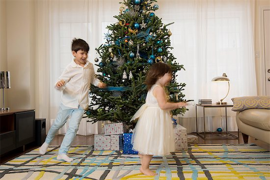 Children playing around Christmas tree Stock Photo - Premium Royalty-Free, Image code: 614-06719323