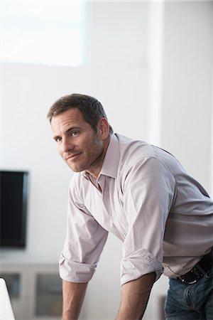 Businessman standing at desk Stock Photo - Premium Royalty-Free, Code: 614-06719365