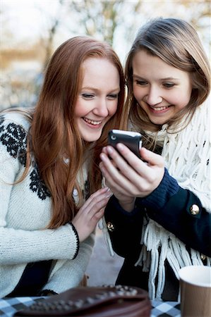 showing - Women using cell phone together Stock Photo - Premium Royalty-Free, Code: 614-06719600