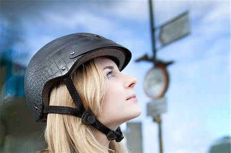 Woman wearing bicycle helmet outdoors Stock Photo - Premium Royalty-Free, Code: 614-06719632
