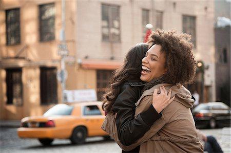 Women hugging on city street Stock Photo - Premium Royalty-Free, Code: 614-06719686