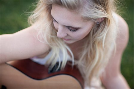 Woman playing guitar in grass Stock Photo - Premium Royalty-Free, Code: 614-06719773