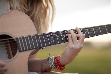 Woman playing guitar in grass Stock Photo - Premium Royalty-Free, Code: 614-06719789