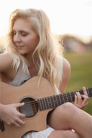 Woman playing guitar in grass Stock Photo - Premium Royalty-Free, Code: 614-06719795