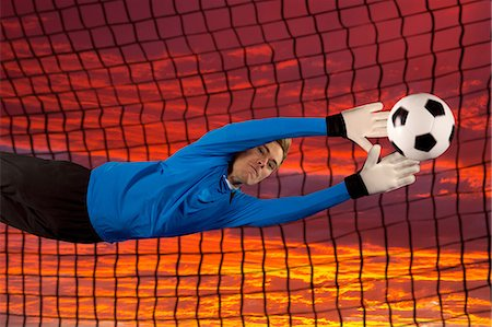 Soccer player deflecting ball in air Stock Photo - Premium Royalty-Free, Code: 614-06719860