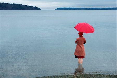Woman with umbrella in rural lake Stock Photo - Premium Royalty-Free, Code: 614-06719877