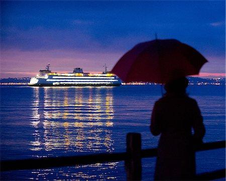 Woman with umbrella admiring cruise ship Stock Photo - Premium Royalty-Free, Code: 614-06719879