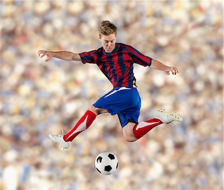 soccer player (male) - Soccer player kicking ball in air Stock Photo - Premium Royalty-Free, Code: 614-06719873