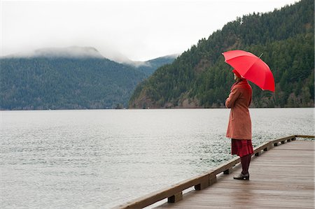 people with umbrellas in the rain - Woman with umbrella on wooden pier Stock Photo - Premium Royalty-Free, Code: 614-06719895