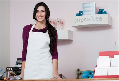 Baker smiling behind counter Stock Photo - Premium Royalty-Free, Code: 614-06719940