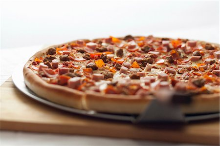 spicy - Close up of shovel and deep dish pizza Stock Photo - Premium Royalty-Free, Code: 614-06720037