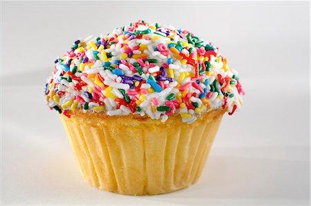 sweet   no people - Close up of rainbow sprinkles cupcake Stock Photo - Premium Royalty-Free, Code: 614-06720046