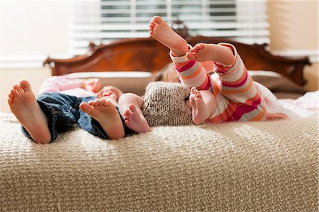 Children laying with infant on bed Stock Photo - Premium Royalty-Free, Code: 614-06720135