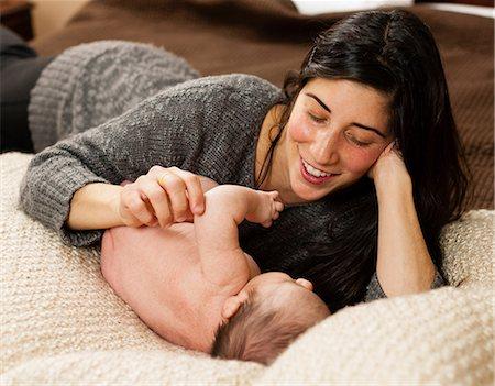 Mother cradling newborn infant on bed Stock Photo - Premium Royalty-Free, Code: 614-06720131
