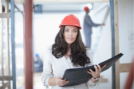 Female architect with portfolio on construction site Stock Photo - Premium Royalty-Free, Code: 614-06814005